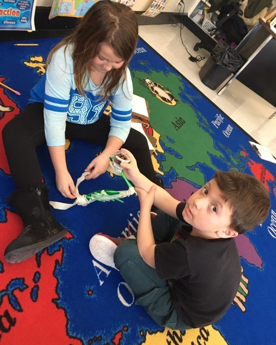 Chloe and Logan work on a tower on St. Patrick's day.